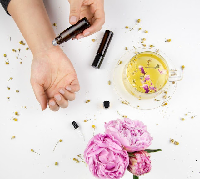 An essential oil rollerball with roses and dried herbs