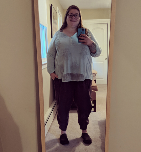 image of me standing in a full-length mirror in my guest room, with my hair down, wearing grey-framed glasses, a light turquoise blouse, dark grey trousers, and grey shoes