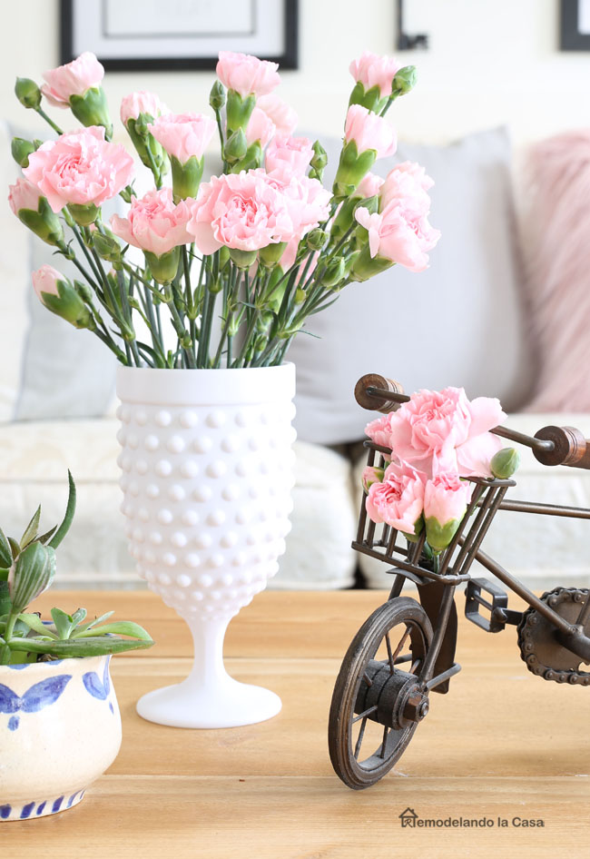 pink carnations in milk glass and little decor bicycle. Coffee table vignette