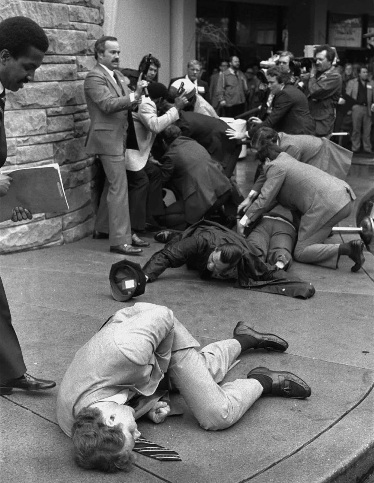 Secret Service agent clutching his stomach after being shot during the assassination attempt of President Ronald Reagan.