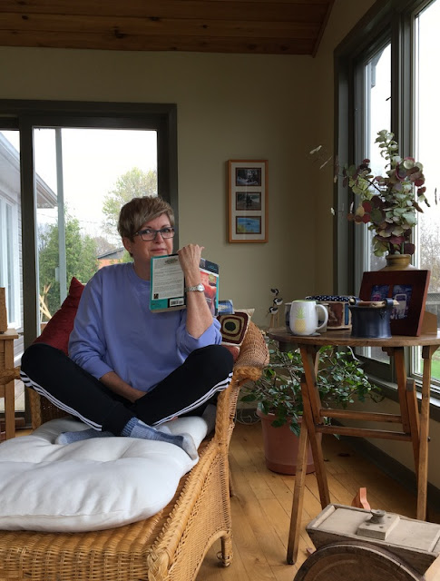 woman in sweatpants and sweatshirt sitting with legs folded and a book in her hands