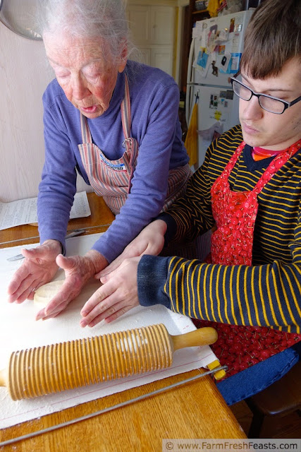 image of grandmother showing grandson how to shape lefse before rolling out the dough