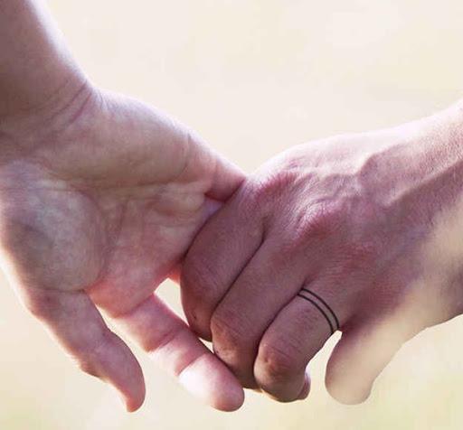 Um preto par de linhas envoltório em torno de que o portador do anel do dedo e funcionar como uma banda de casamento neste tatuagem.