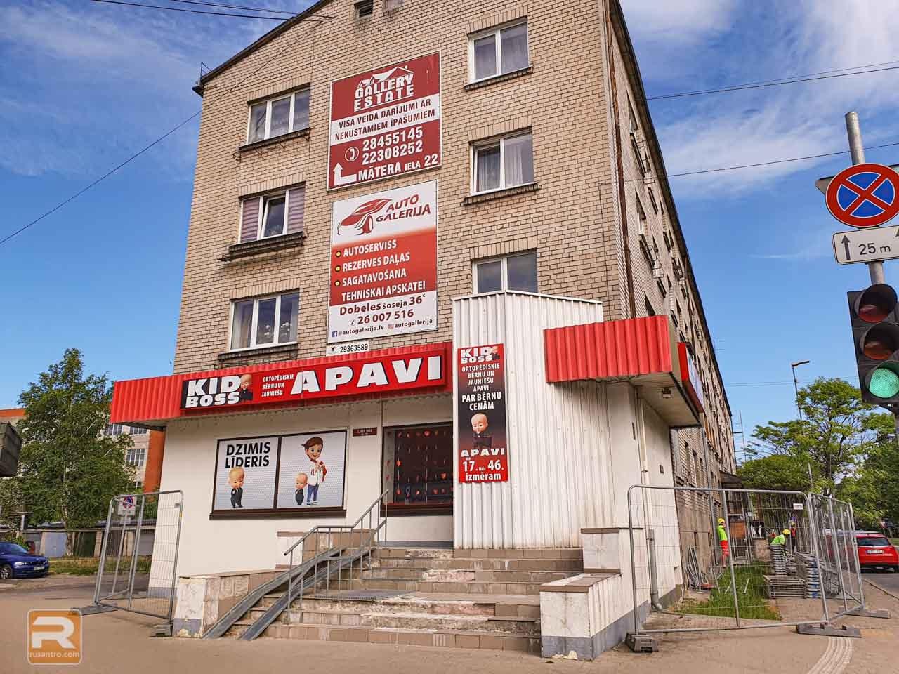 Ķieģeļu piecstāvu dzīvojamā māja ar reklāmas izkārtnēm uz tās fasādes Jelgavā
