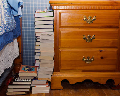 bedroom dresser, with a huge stack of books next to it