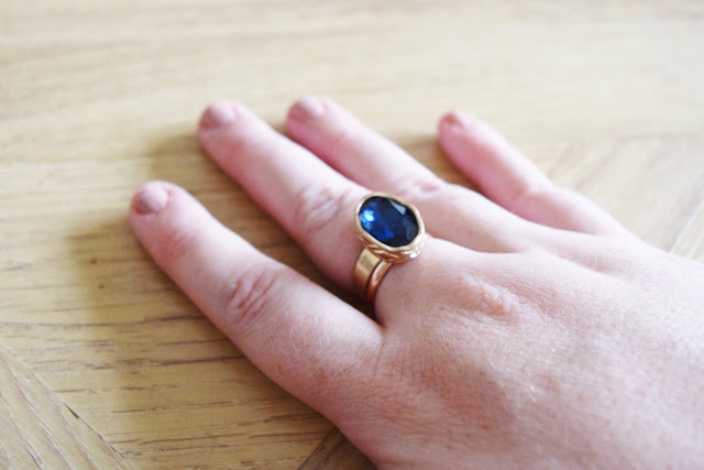blue gem ring on finger