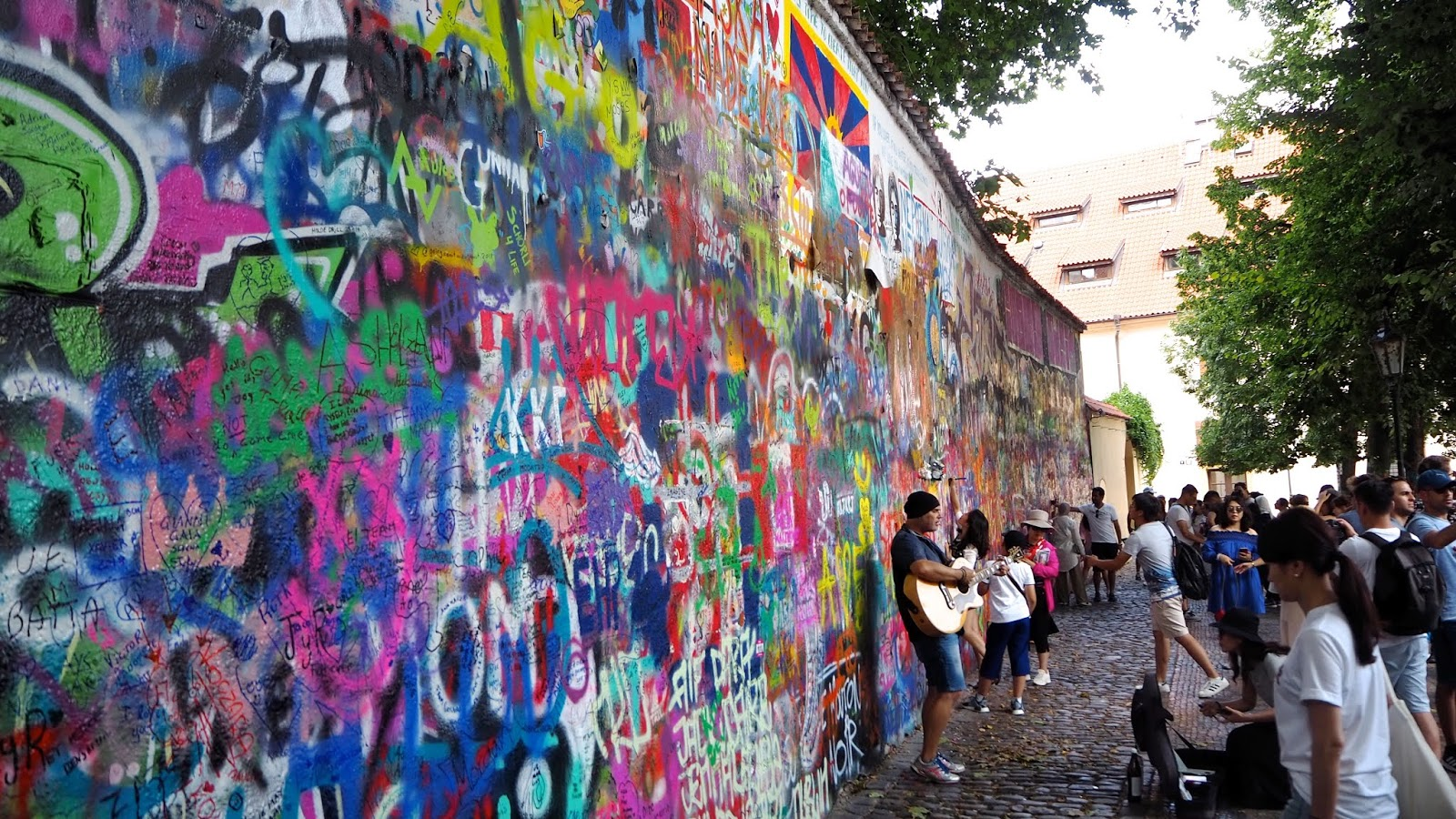 Crowds and musician in front of graphiti wall