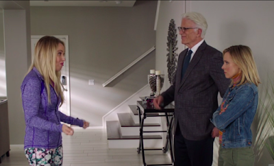 A woman in a purple athleisure jacket with blonde hair stands across from Eleanor and Michael. Eleanor's face is stony. The background is the interior of a house painted gray.