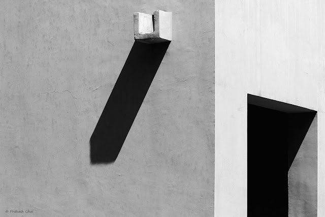 A Black and White Minimalist Photo created using the Shadow of and open door and a water outlet at Jawahar Kala Kendra, Jaipur.