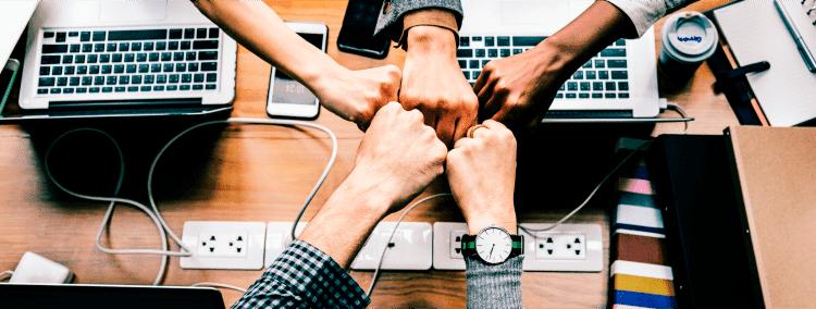 mãos se unindo sobre computadores fazendo menção a união e força dos grupos