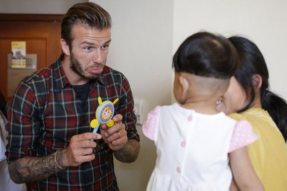 David Beckham pulls funny face for children in Chinese hospital