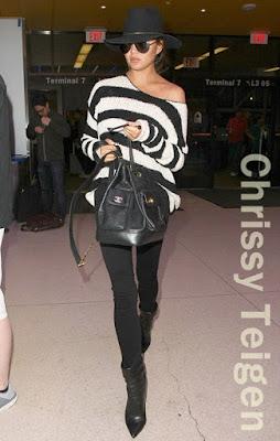 クリッシー・テイゲン(Chrissy Teigen)は、ジャネッサレオン(Janessa Leone)のハット、アンソニートーマスメリロー(ATM Anthony Thomas Melillo)のセーター、フレーム(Frame)のスキニージーンズ、シャネル(Chanel)のバックパックを着用。