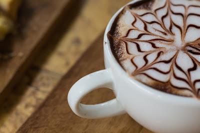 Xícara branca de cappuccino com desenho na superfície