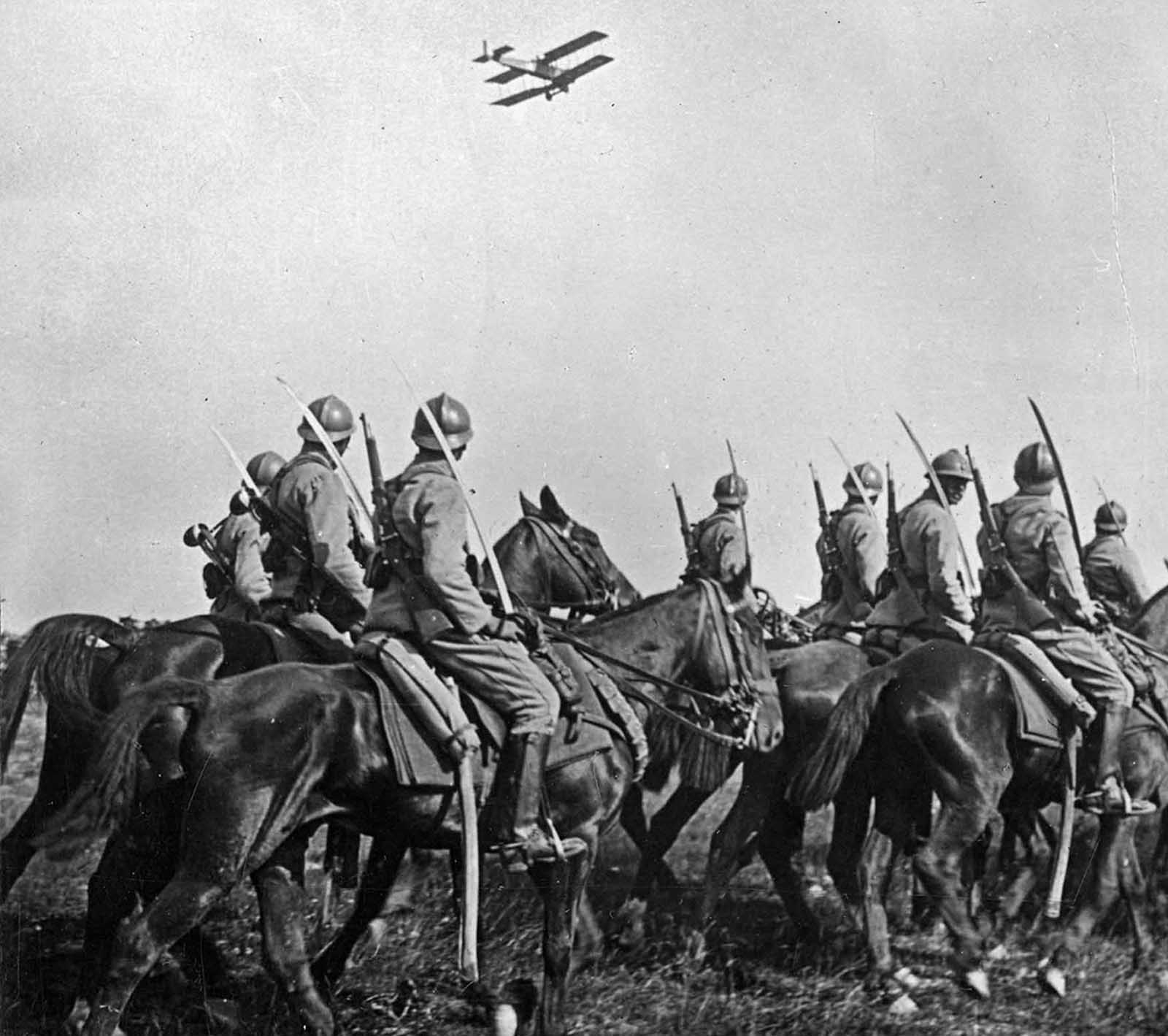 French Cavalry observe an Army airplane fly past.