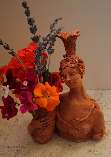 lady, plumes, basket, sarah, myers, art, arte, artist, terracotta, sculpture, vase, escultura, skulptur, flowers, bouquet, arrangement, beautiful, feathers, woman, figurative, decor, decorative, contemporary, modern, red, earthenware, clay, face, eyes, cornucopia, lavender, nasturtiums, jasmine, bougainvillea, spring, printemps, primavera, handmade, bright, pink, yellow, orange, flores