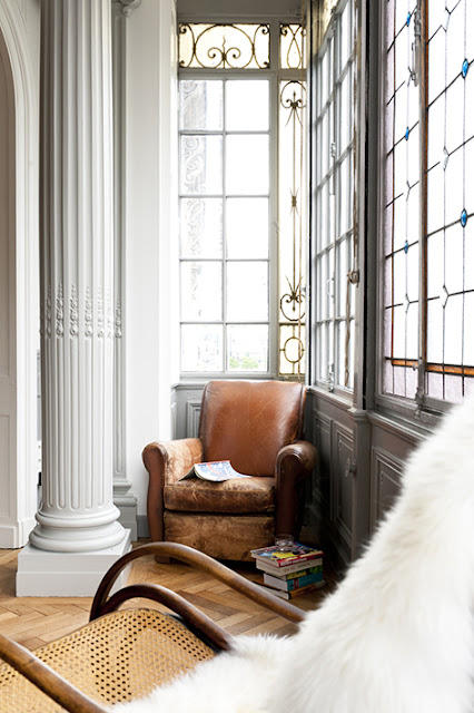fauteuil club auprès d'une fenêtre en saillie faite d'anciens vitraux