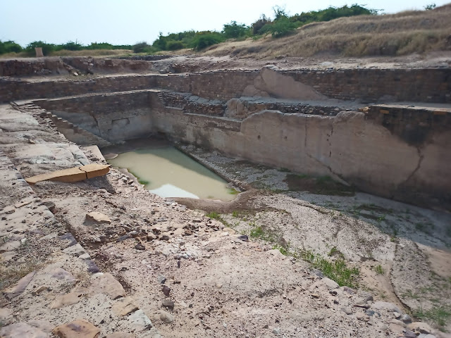 Reservoir cut into ground at Dholavira with stairs leading down and some water collected inside