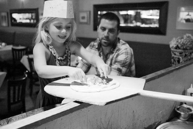 Little girl prepares her pizza for the wood fire oven at Mezza.