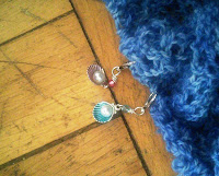 A close up of two locking stitch markers.  Each stitch marker charm is a half-shell with a purl inside.  One is a teal blue, the other a pale pink.