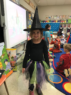 Young girl dressed as a witch in a black hat and purple green and black skirt