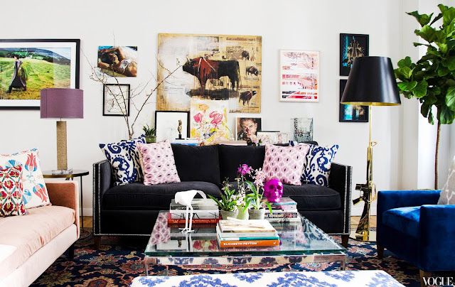 NYC apartment with madeline weinrib throw pillows on a charcoal gray velvet sofa with nailhead trim, glass coffee table, brass floor lamp, large patterned rug with walls covered in art