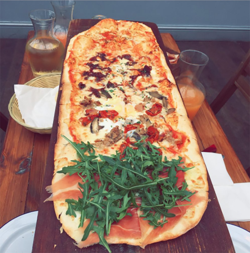 Metre long pizza on board with rocket topping