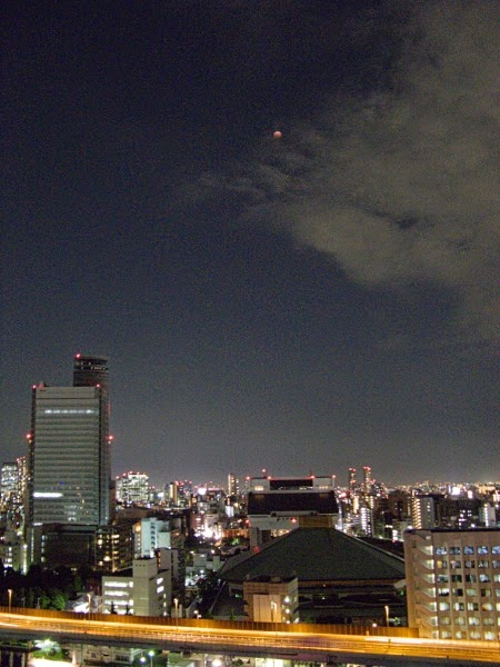 Red, fully eclipsed moon over the Kokugikan and Edo Tokyo Museum, Tokyo.