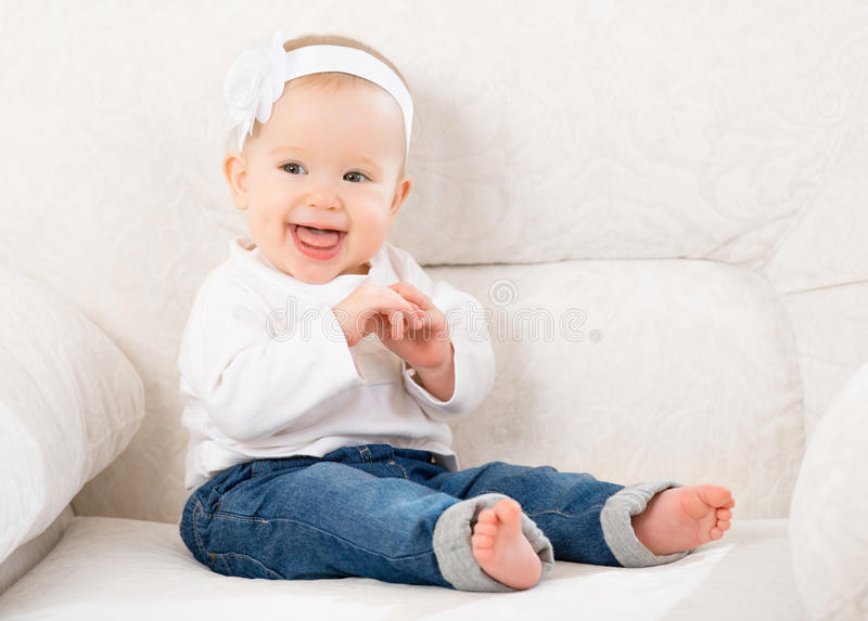 happy-little-baby-girl-laughing-sitting-sofa-jeans-white-blue-30388733.jpg