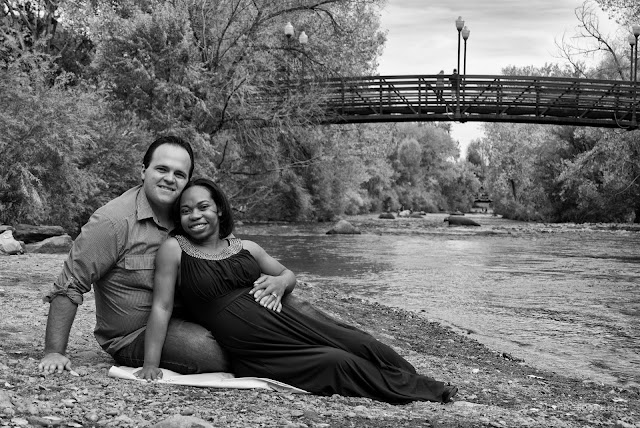 a stunning black and white portrait of an expecting couple along a river in Colorado
