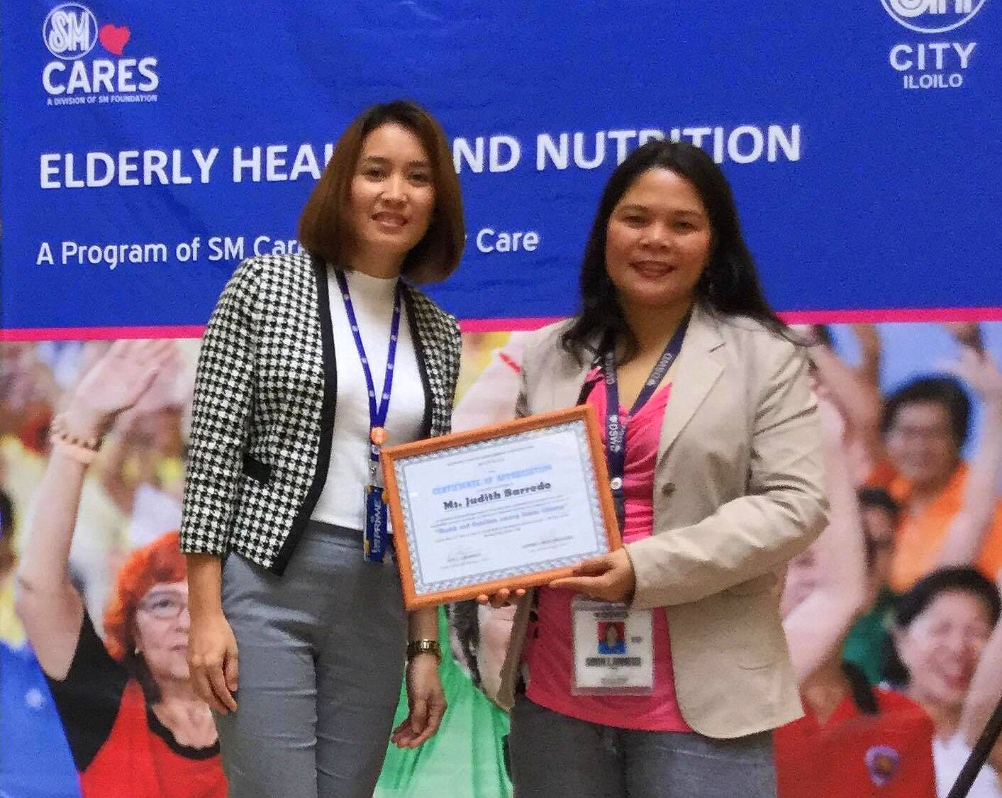 SM City Iloilo Asst. Mall Manager Jasmine Linn Maquiling presents a plaque of apprciation to Ms Judith Barredo of DSWD 6