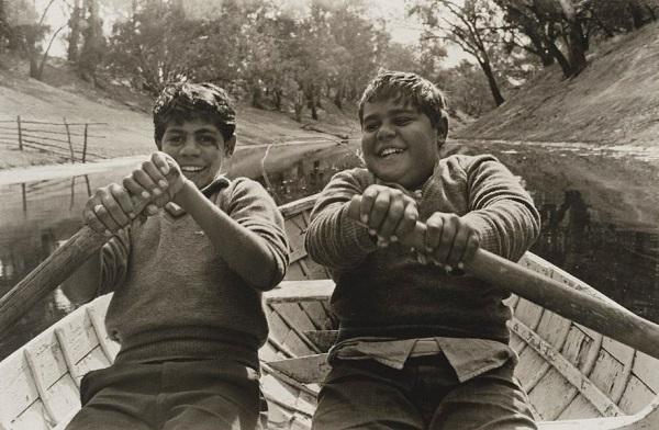 Vintage cool foto: dos niños reman felizmente por el río.