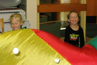 children playing with a parachute and balls