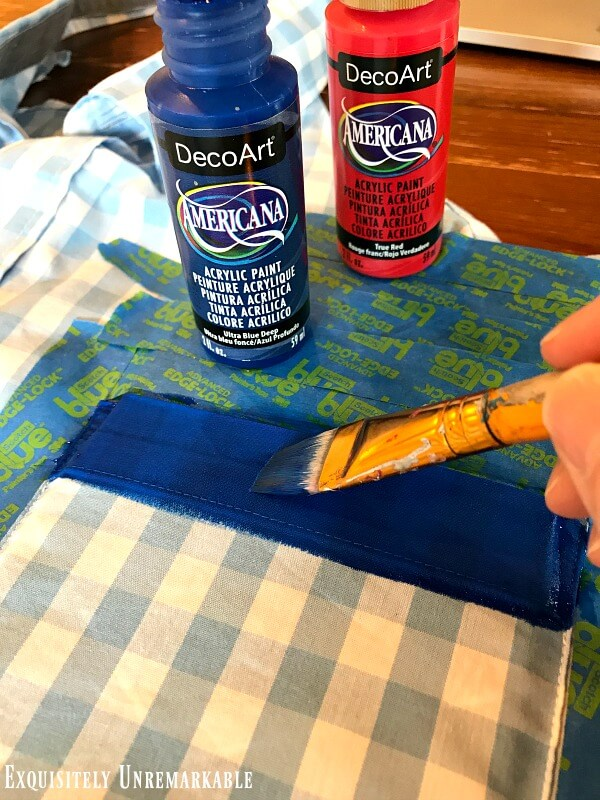 Painting a blue stripe on the pocked of a men's gingham shirt.