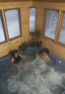 Two ladies sitting in an enclosed hot tub with windows.
