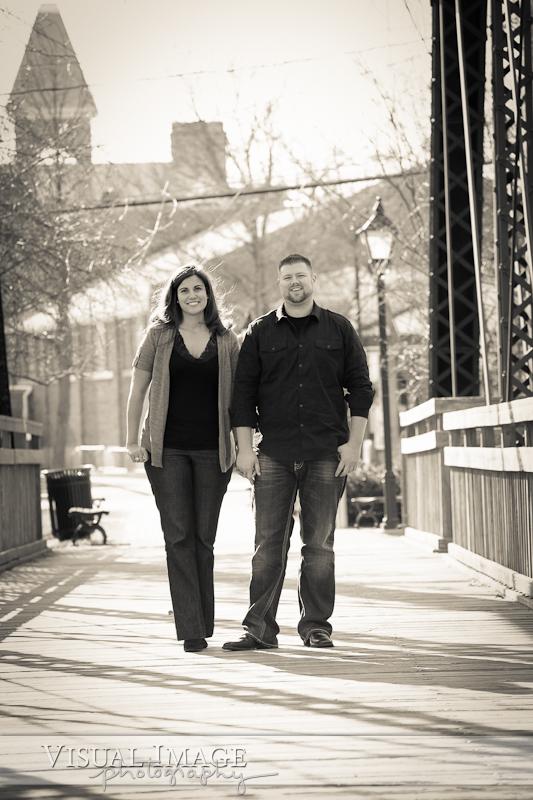 Couple holding hands on bridge in downtown Cedarburg