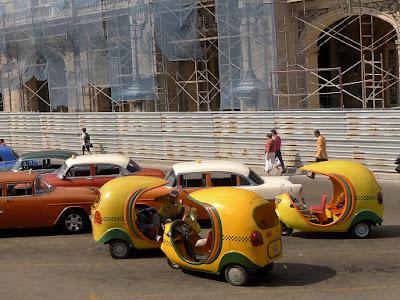 Kuba, Cocotaxis vor dem Kapitol in Havanna, drei knallgelbe Cocotaxis neben Straßenkreuzern, ebenfalls Taxis.