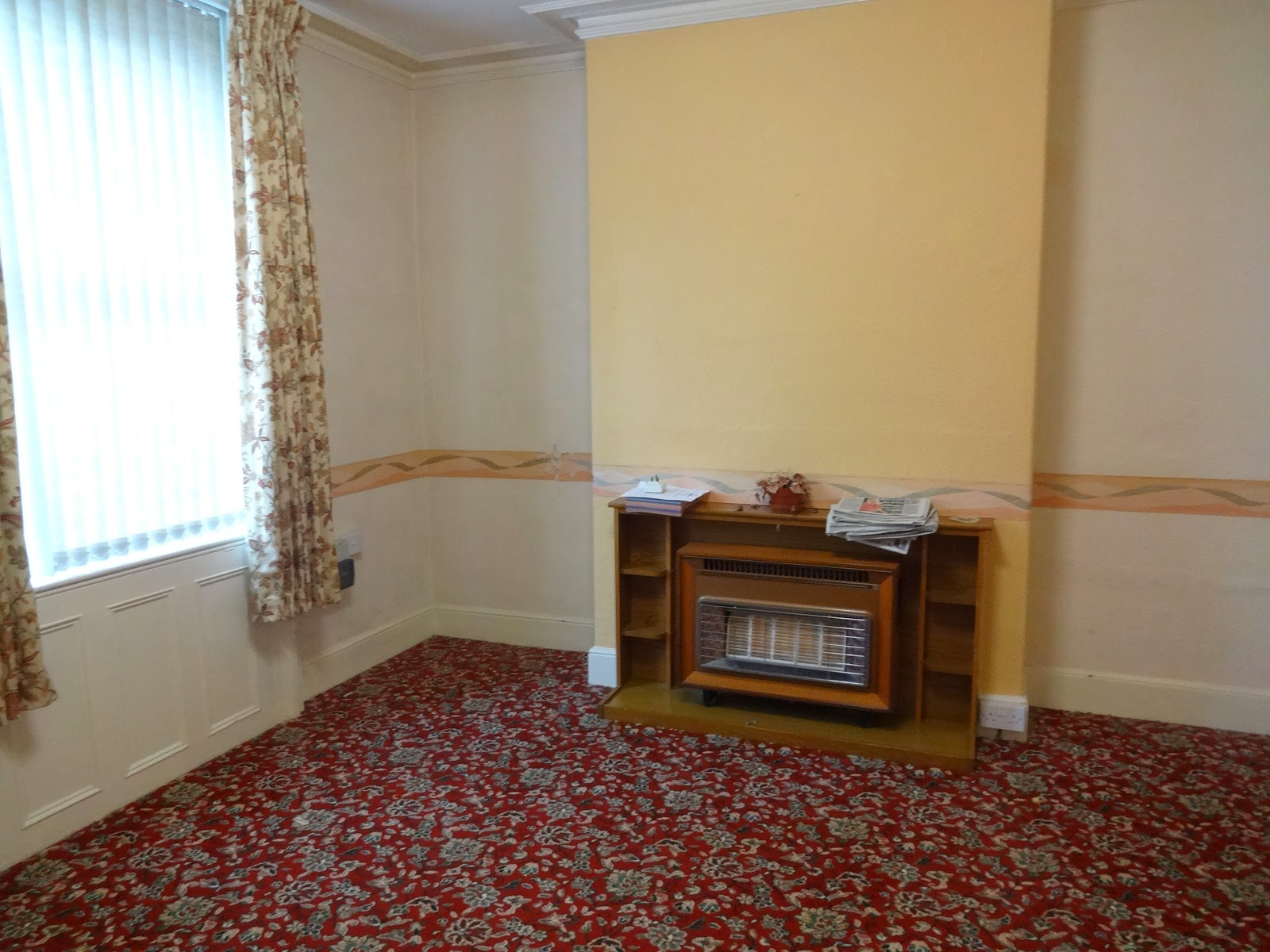 retro living room with floral carpet and old gas fire
