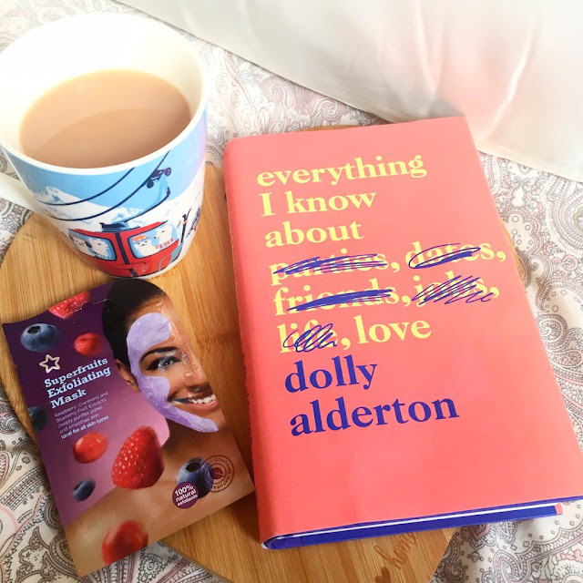 Silk pillowcase in the background, heart chopping board in front with book, face mask and cup of tea