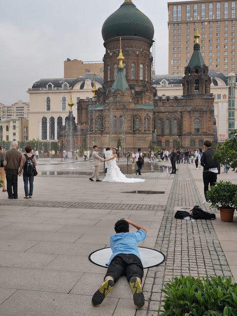 photographer and couple taking wedding photos next to the Saint Sophia Cathedral in Harbin