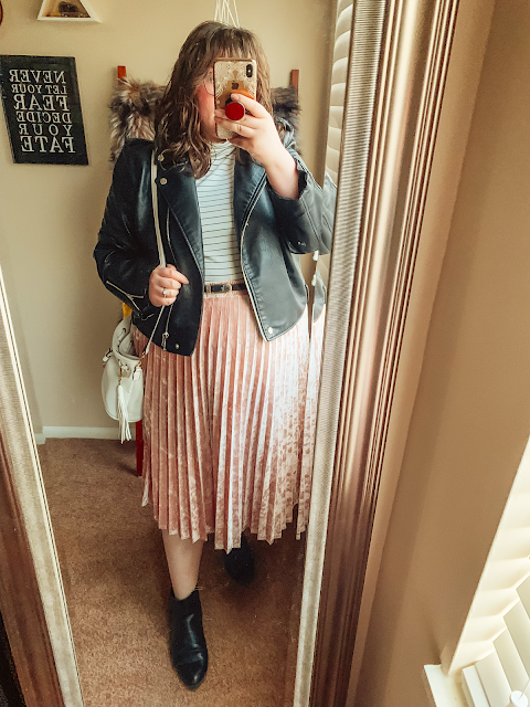 A mirror selfie of an outfit consisting of faux leather black moto jacket, a white and black striped turtleneck tucked into a pink velvet pleated midi skirt.