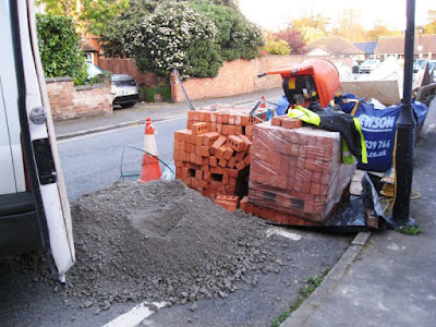 Rubble, bricks, cement mixer, skip on the road outside the house