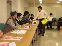 机をまわって参加者にモノをわたす広瀬さん
