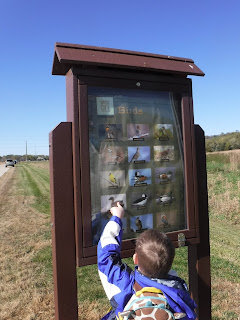 boy pointing at sign with pictures of ducks and geese at Prairie Park in Sioux City, Iowa