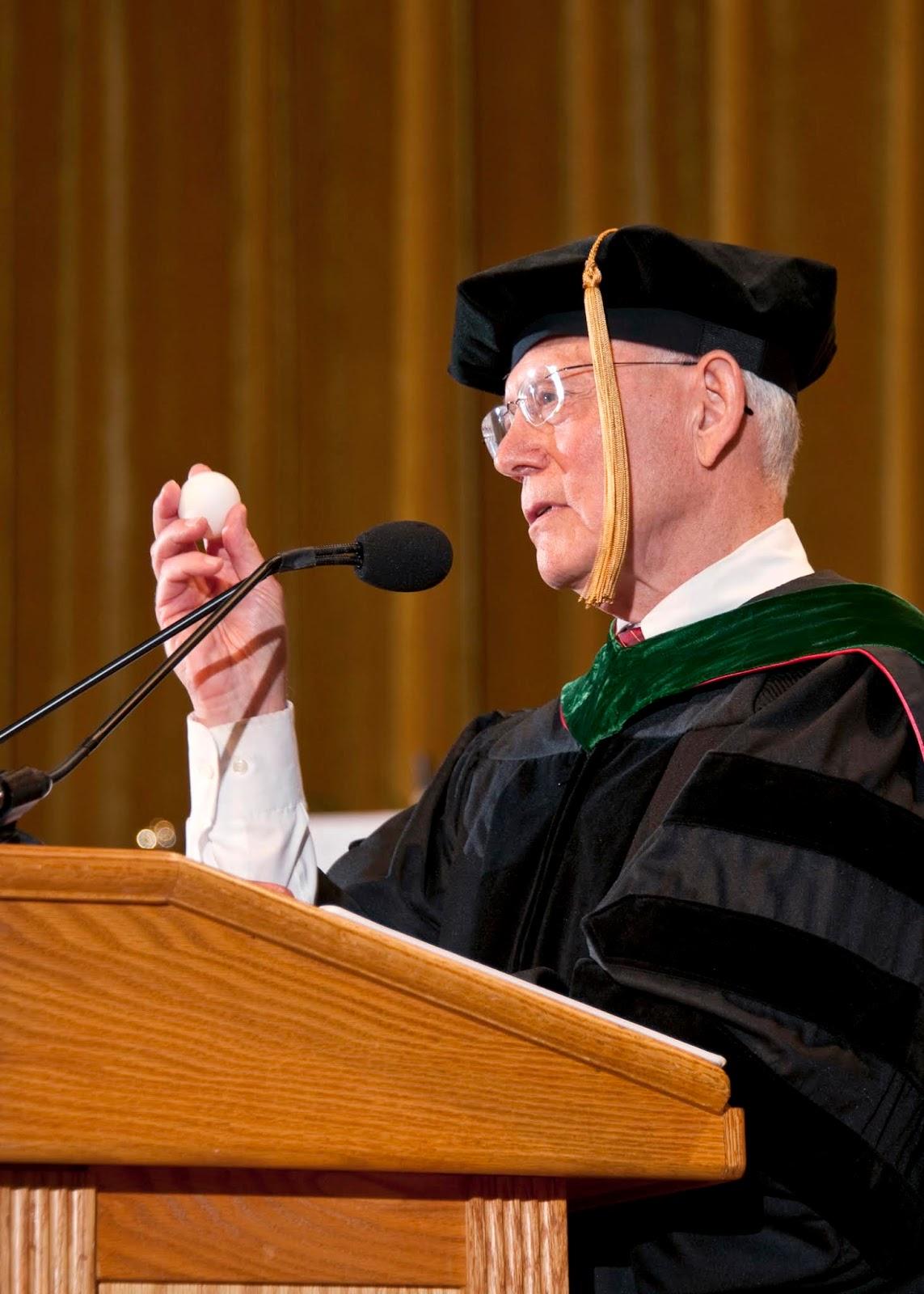 The keynote speaker holds an egg