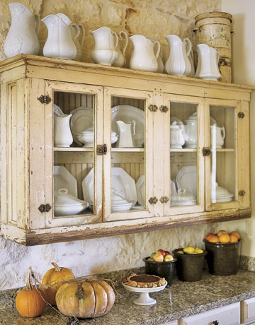 Vintage vases and dishes stored in this gorgeous rustic cabinet give this fall themed kitchen an inviting look