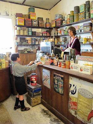 Full-scale model of the interior of a 1930s shop, with a shopkeeper serving a school boy in uniform.