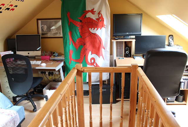 his and hers office space with a desk either side of the room divided by a Welsh flag