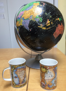 two mugs decorated with antique maps and an out-of-date globe