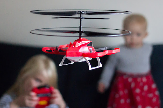 The red, white and black drone in focus in the foreground with 2 children out of focus in the background, one holding a red and black remote control