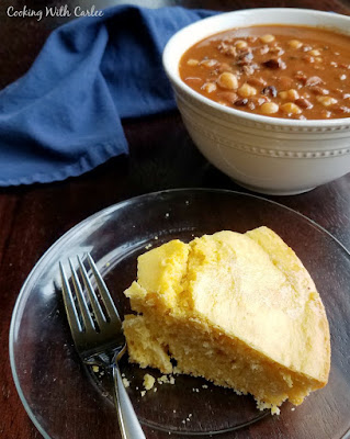 slice of cornbread on plate in front of bowl of chili